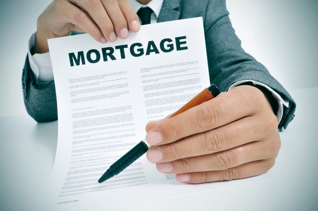 man wearing a suit sitting in a table showing a mortgage loan contract and where the signer must sign