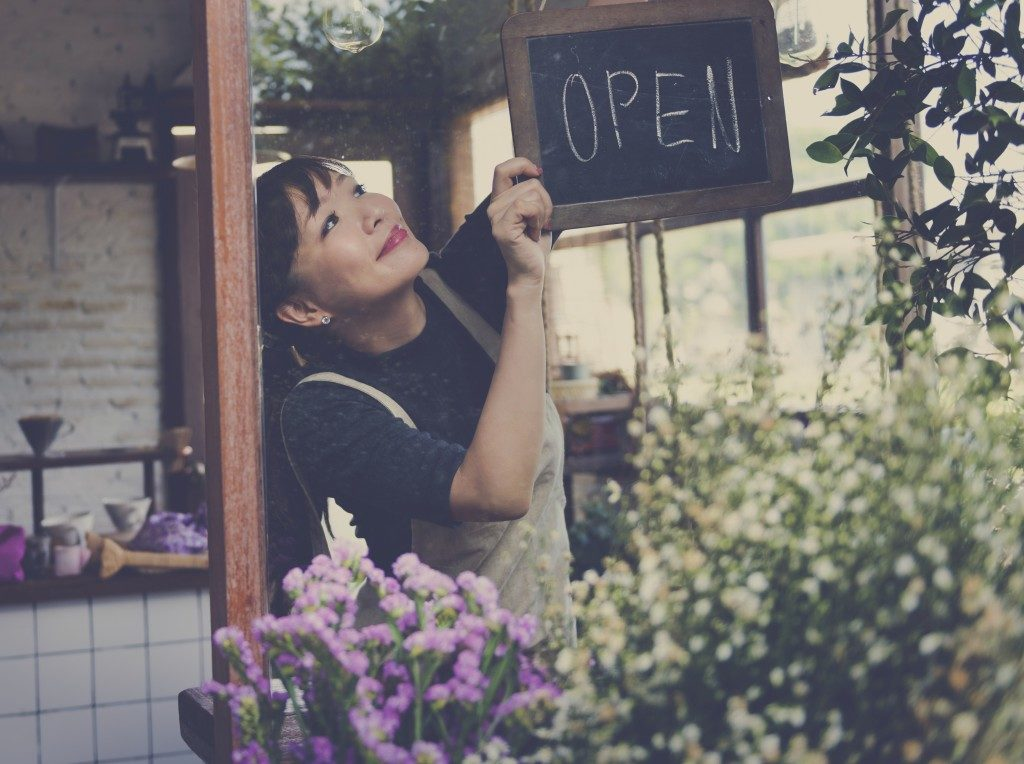 flower shop owner putting the open signage on her shop