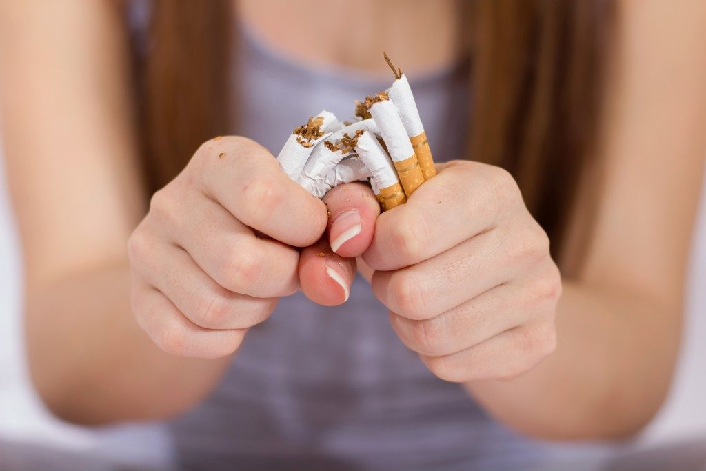 girl holding a handful of cigarettes