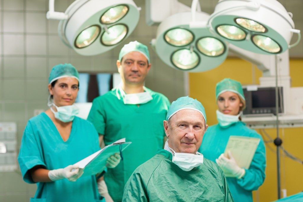 nurses and doctors wearing green medical gowns inside a surgery room