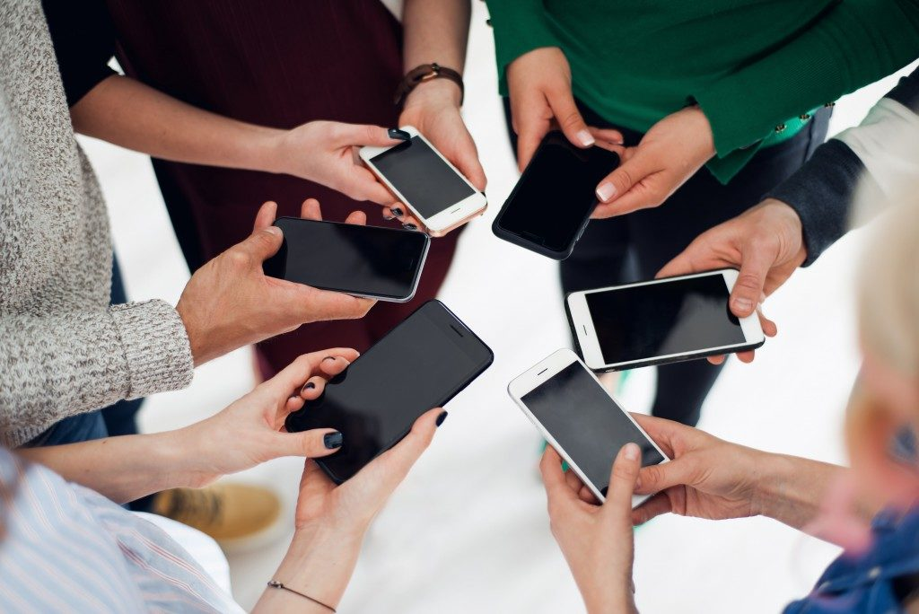 Shot of a group of colleagues using their smartphones in a huddle