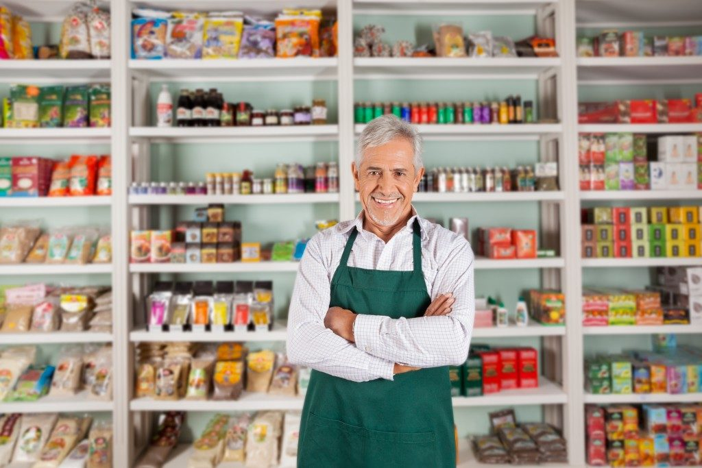 Portrait of happy senior male owner standing arms crossed against shelves