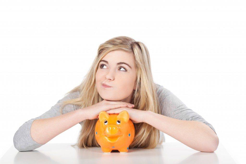 Image of girl posing with piggy bank