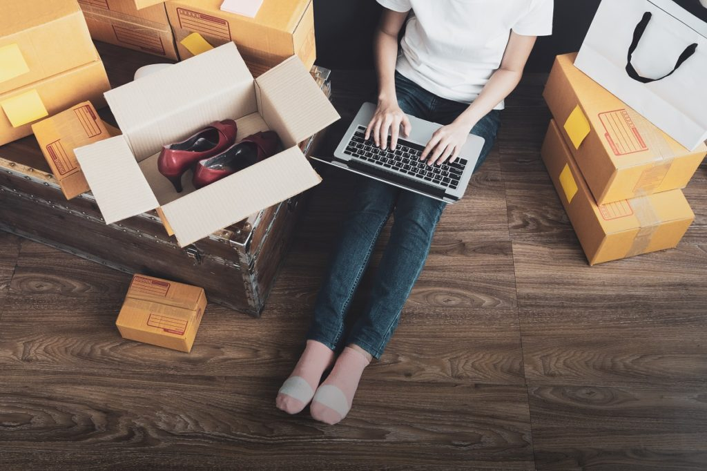 woman checking online orders surrounded by boxes